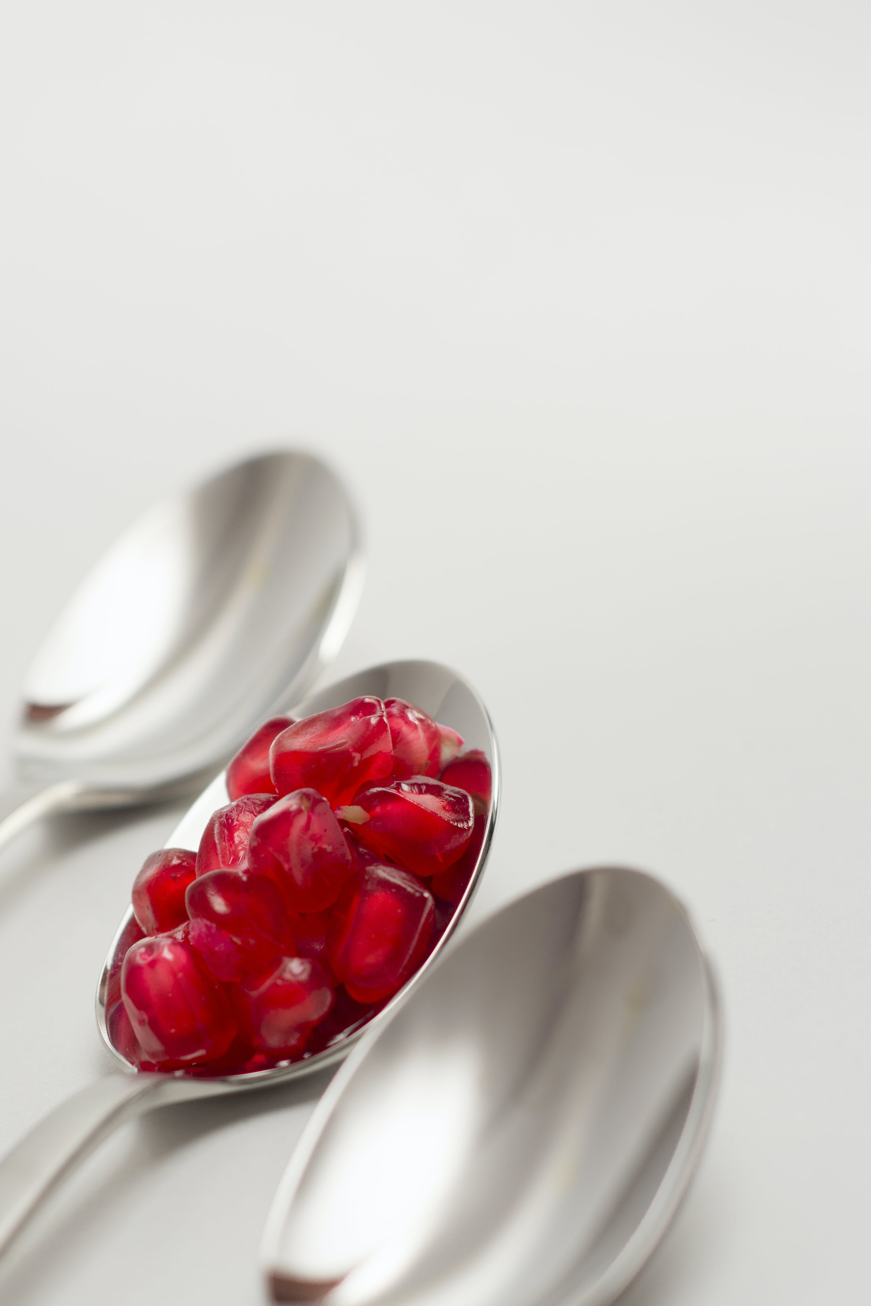 Pomegranate Seed on Spoon Between Empty Spoons