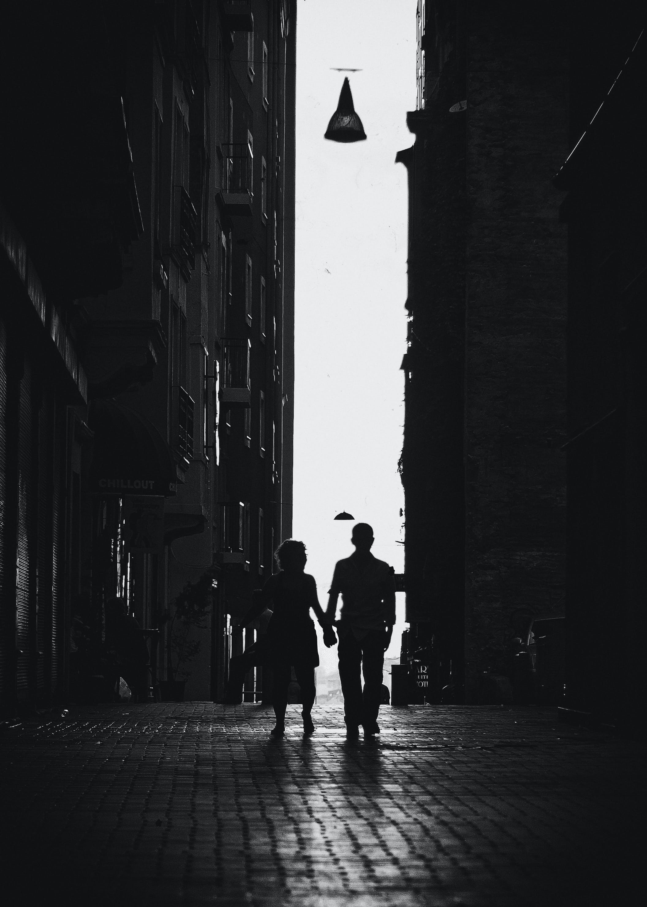 Photo Of Man And Woman Walking In Alley