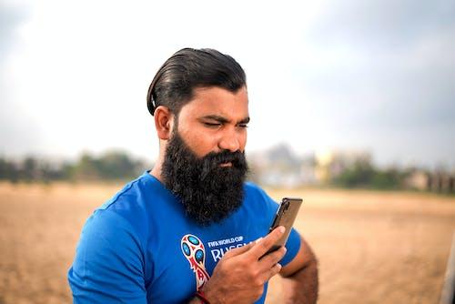 Fotos de stock gratuitas de azul, barba larga, buscando móvil, cabello