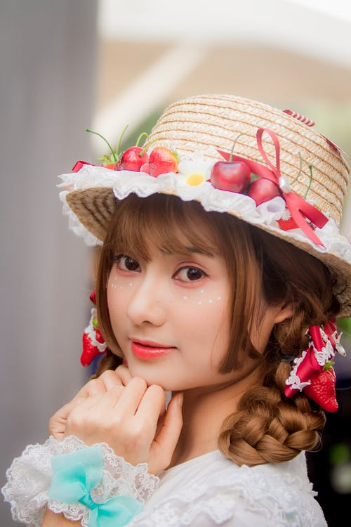 Close-Up Photo Of Girl Wearing Straw Hat