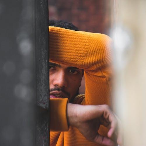 Man In Orange Long Sleeve Shirt Leaning On Wall