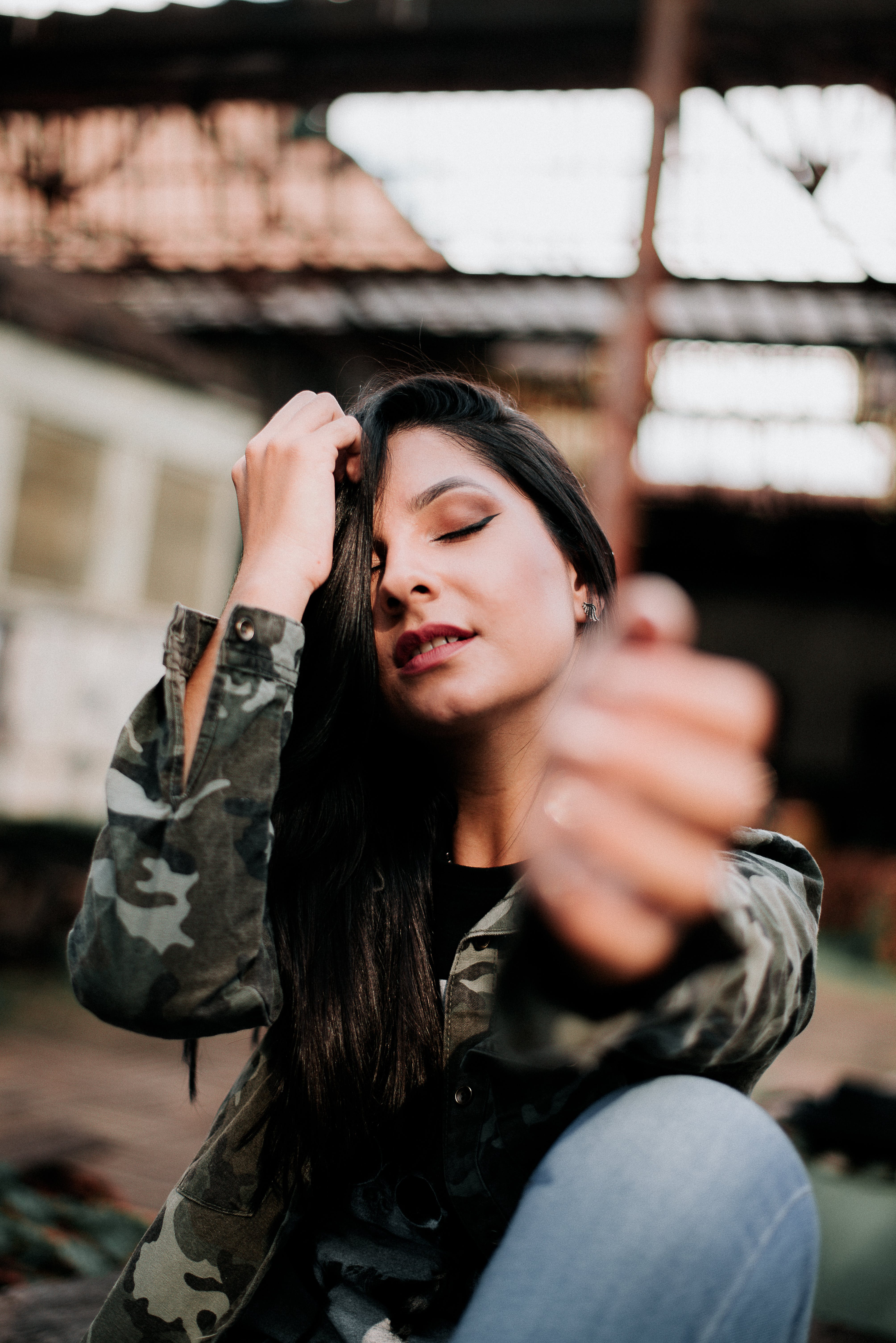 Photo of Woman in Camouflage Jacket Posing with Her Eyes Closed