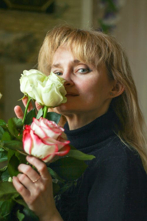 白とピンクのバラの花を保持している女性