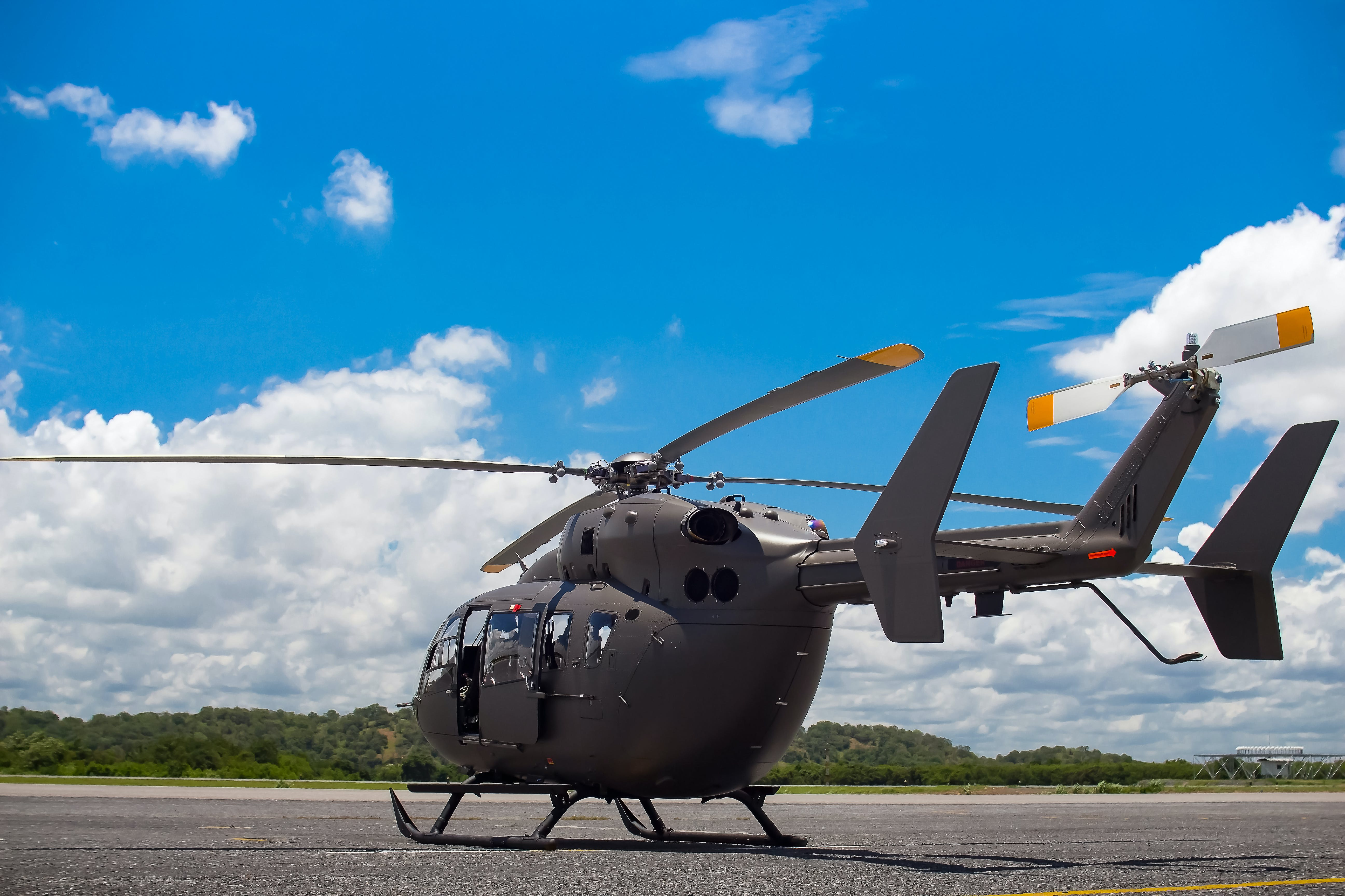 Gray Helicopter on Gray Concrete Pavement Under Blue Sky