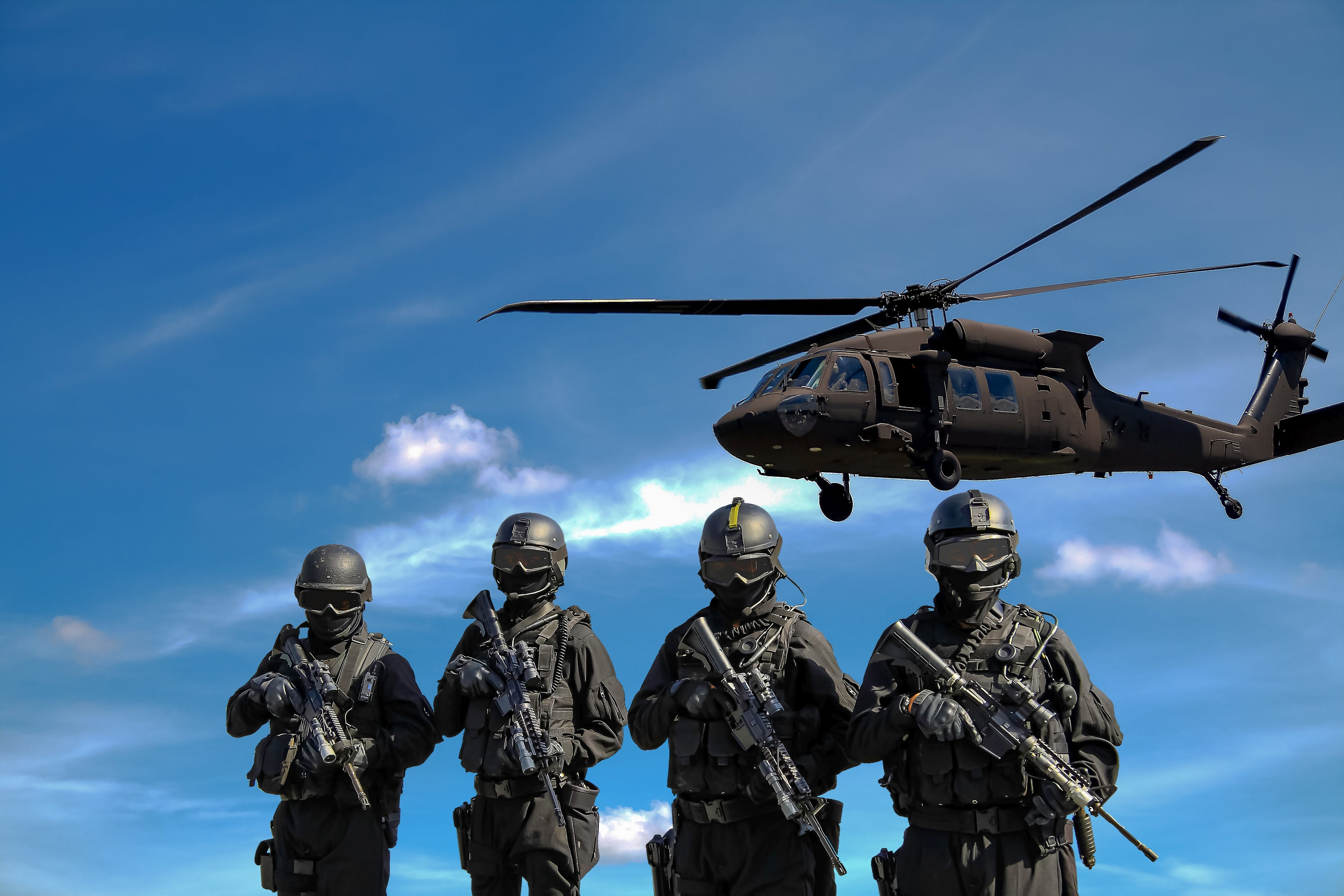 Four Soldiers Carrying Rifles Near Helicopter Under Blue Sky