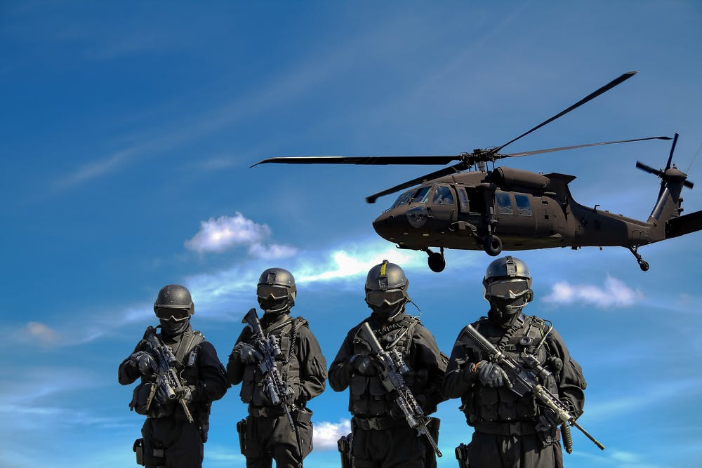 Four soldiers carrying rifles near helicopter | Photo: Pexels