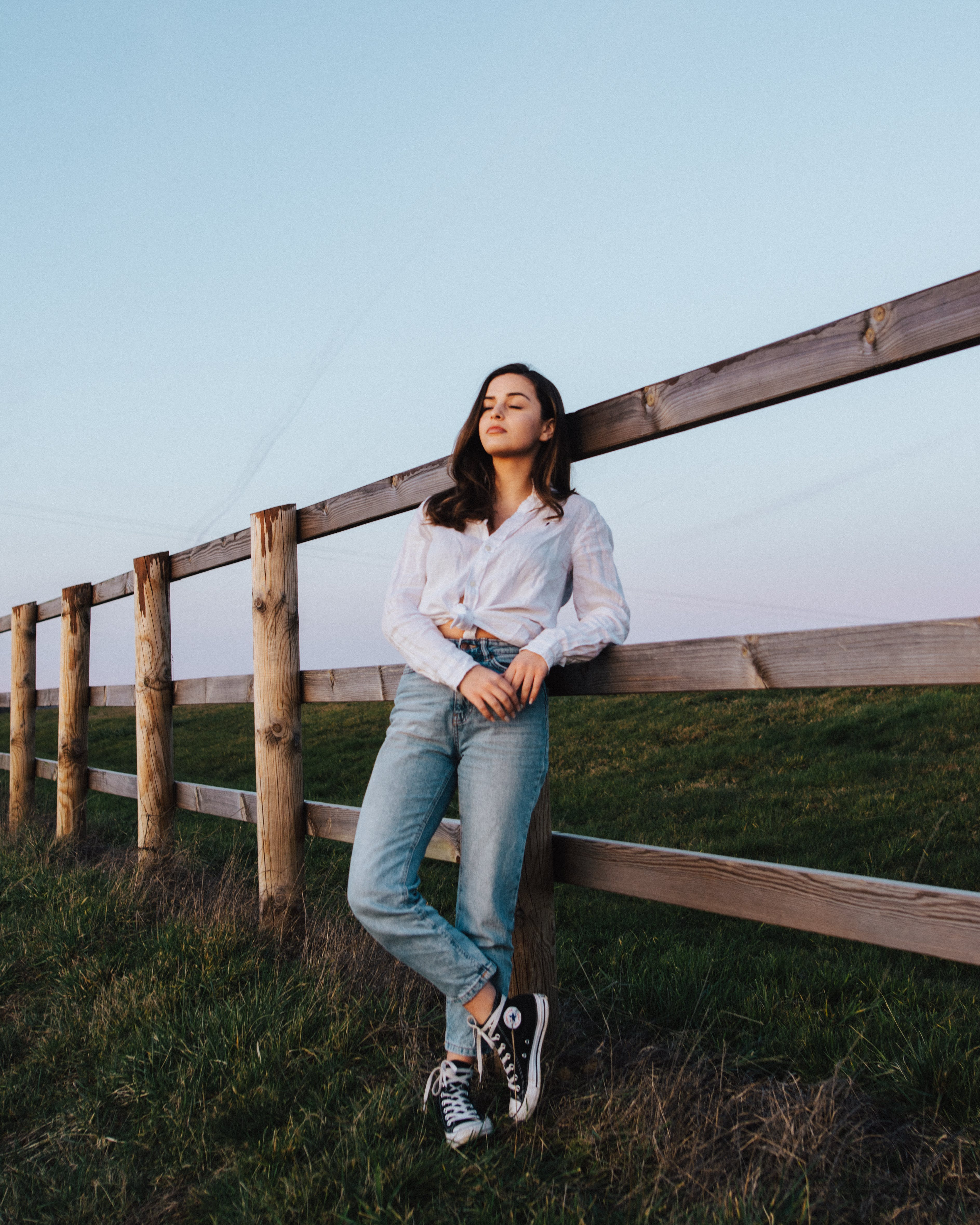 Woman Leaning on Wooden Fence While Standing on Grass Field