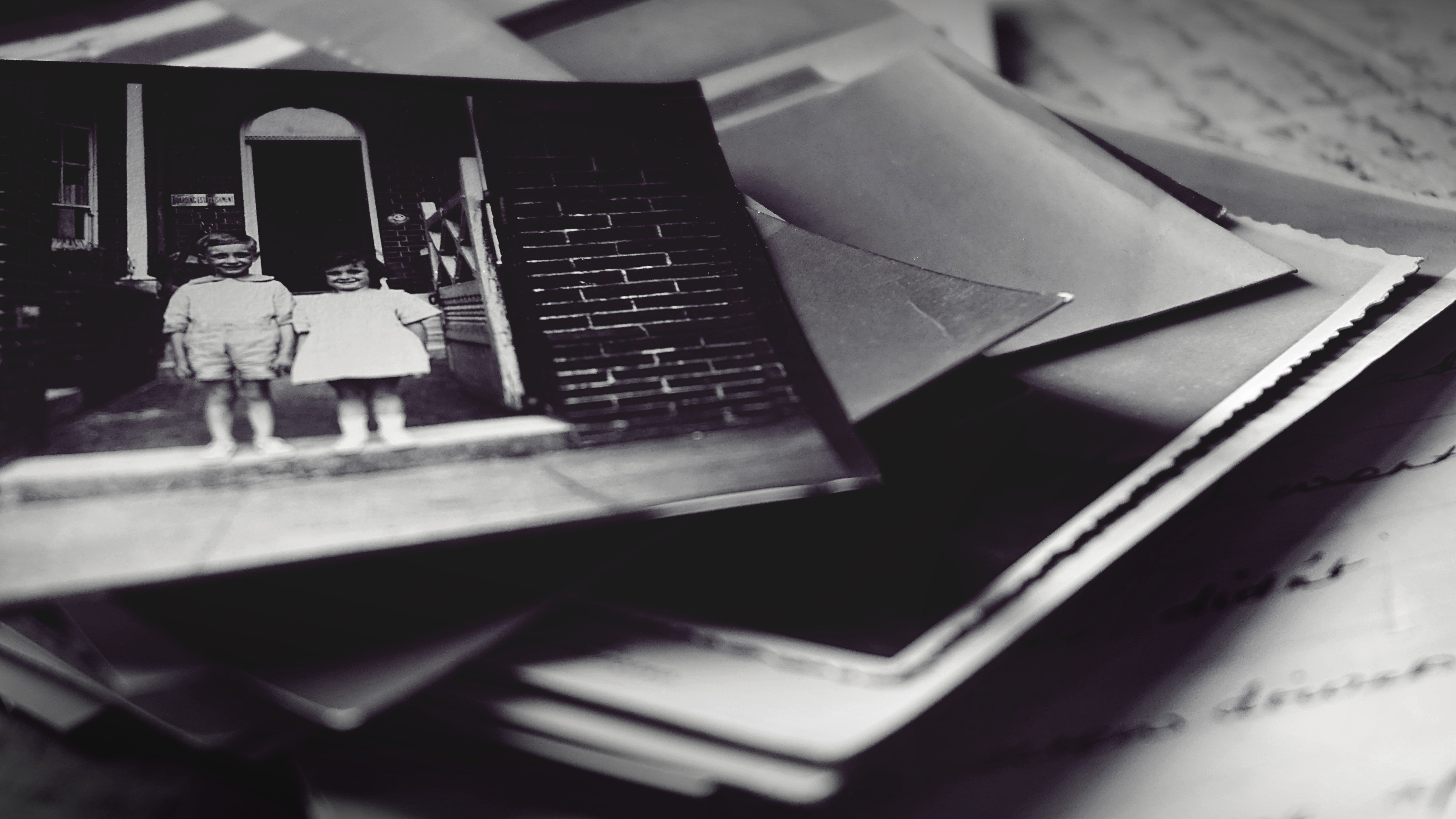 Grayscale Photography Of Pile Of Photographs