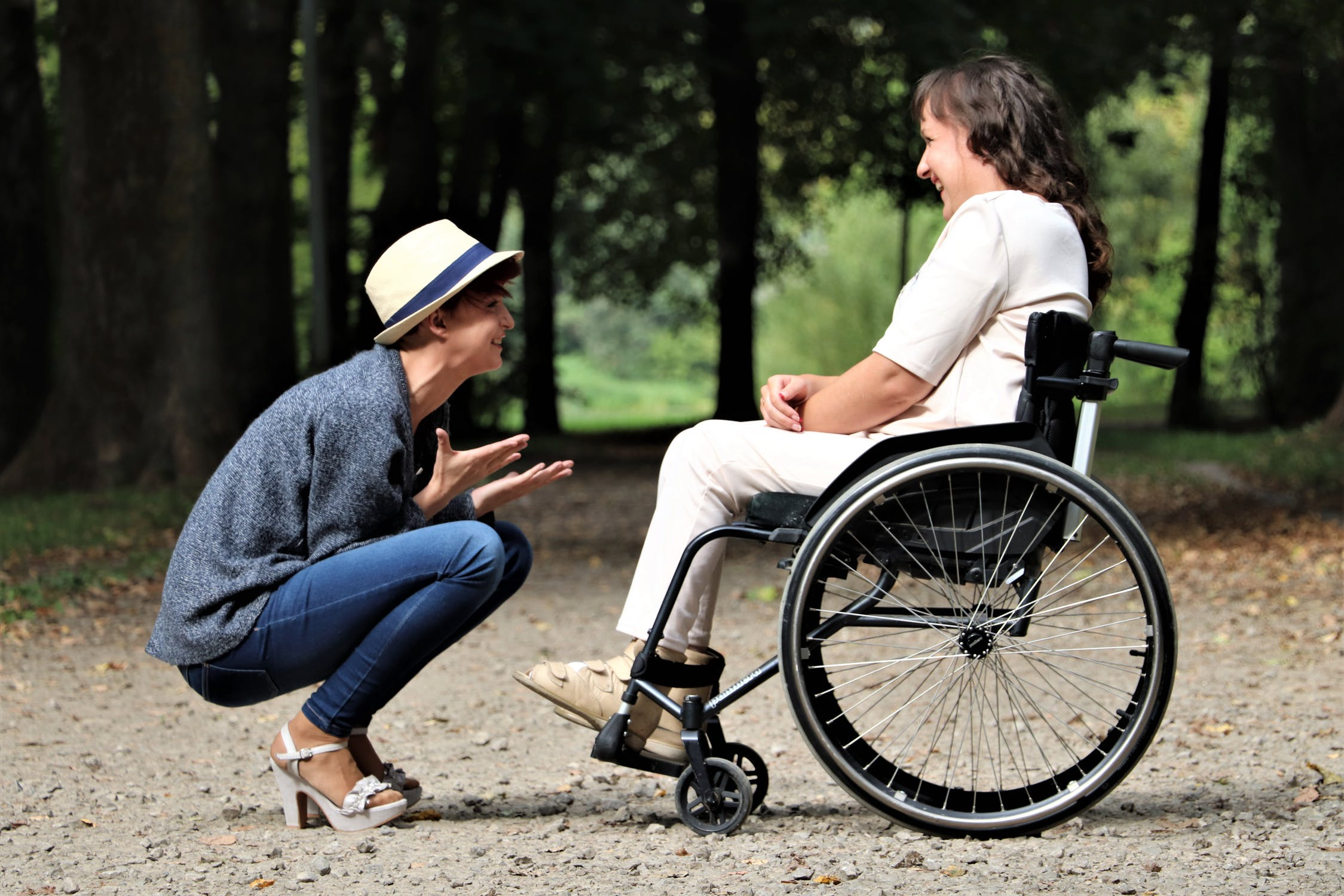 A woman who uses a wheelchair laughing with a friend. Photo by pexels user Judita Tamošiūnaitė. Used courtesy of pexels.com.