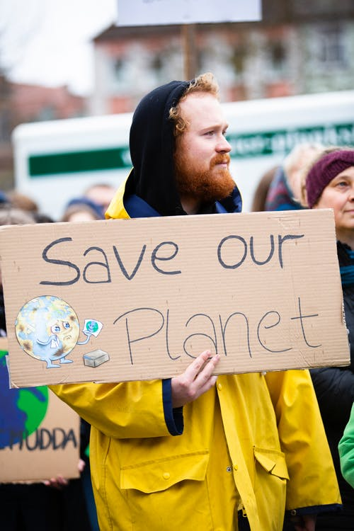 Person Holding Save Our Planet Sign