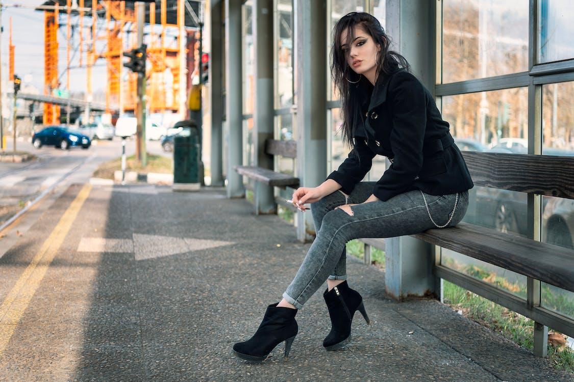 Woman Sitting on Bench While Smoking