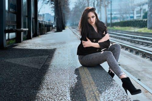 Woman in Black Coat Sitting Near the Train Track