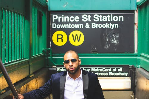 Man Standing Near Prince St Station Sign