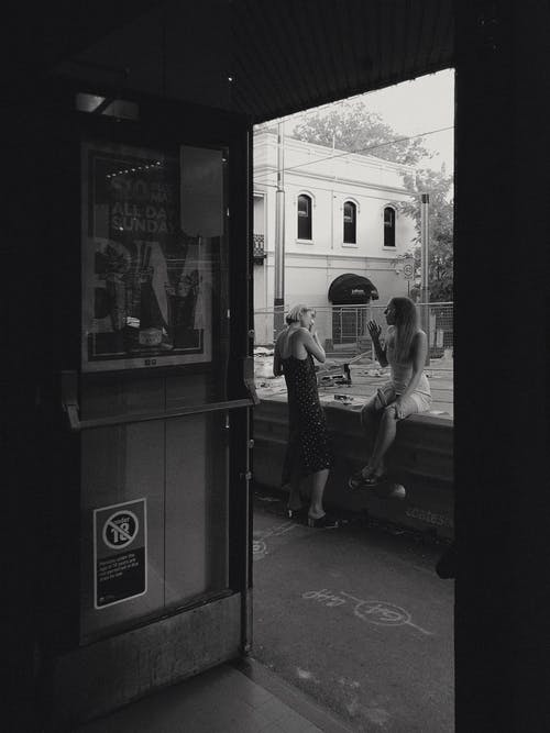 Grayscale Photography of Two Women Near Bar
