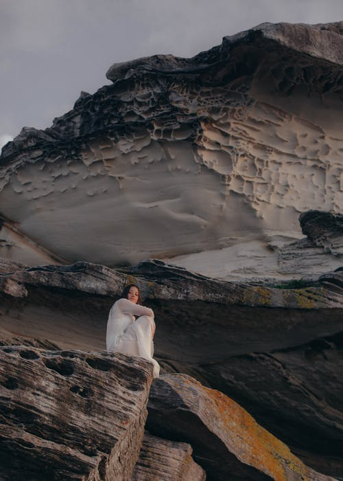 Woman in White Dress Sitting on Top of Rock