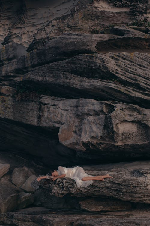 Aerial Photography of Woman Lying on Rock Mountain