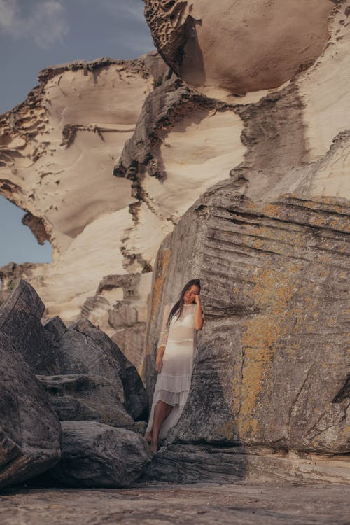 Woman in White Dress Standing on Rock Formation