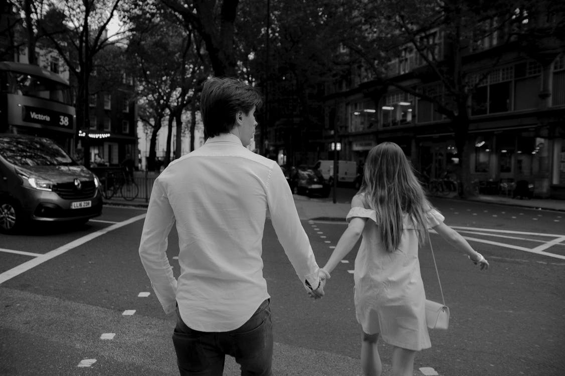 Grayscale Photography of Man and Woman Holding Hands on Road