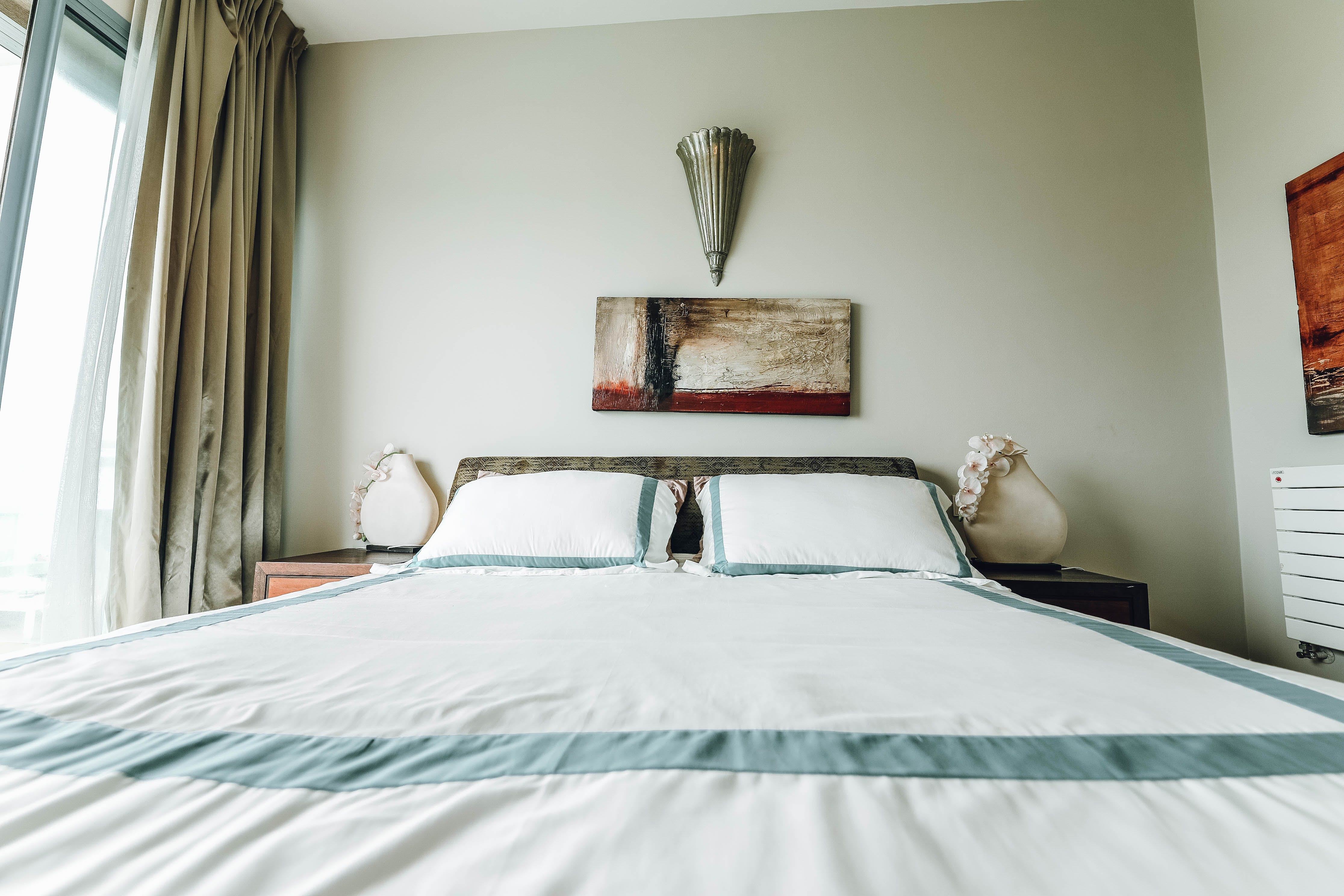 White Bed With Bedspread Near Window
