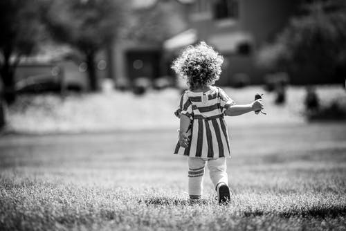 Monochrome Photography of Girl Walking on Grass Field