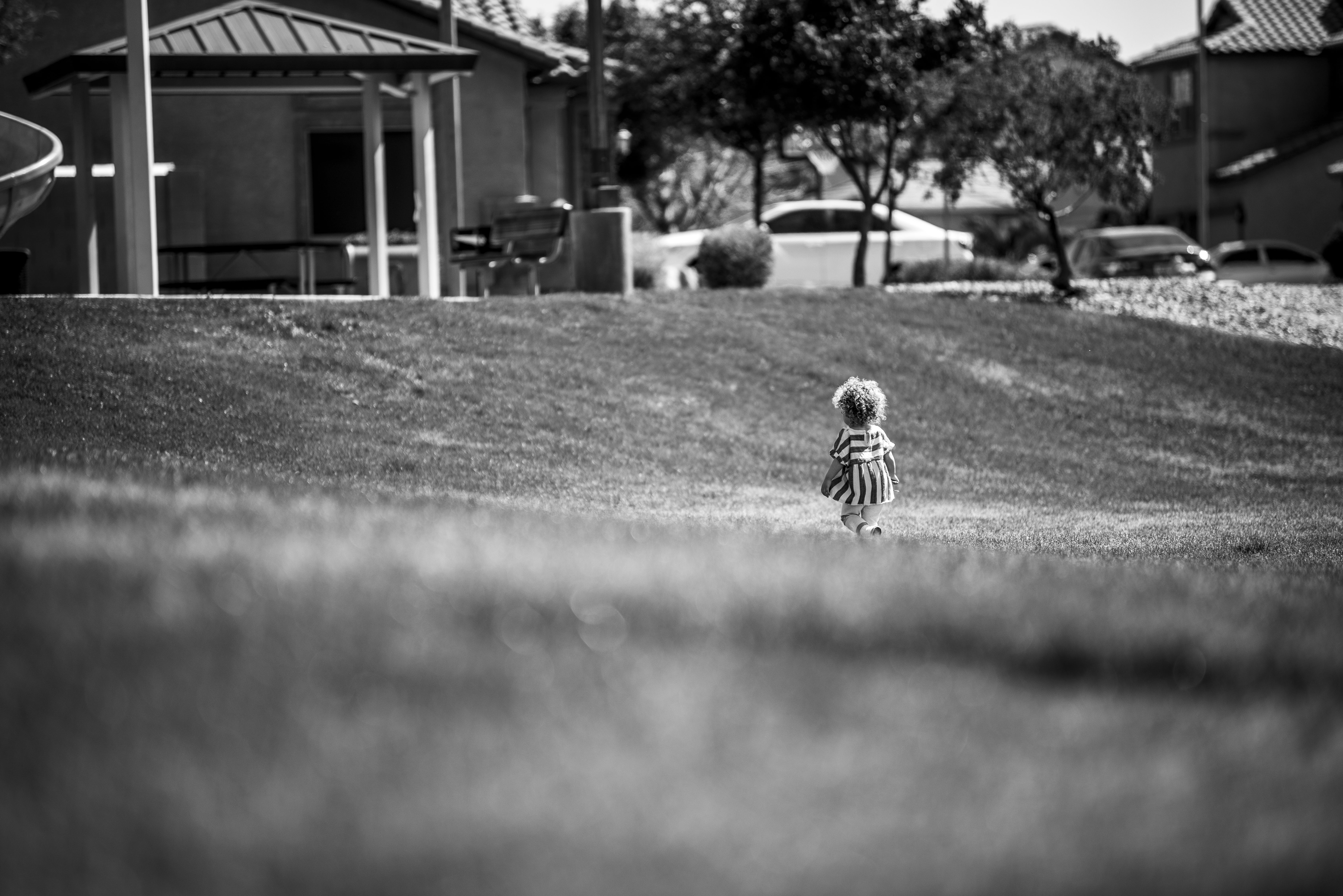 Grayscale Photography of Girl Walking on Grass Field