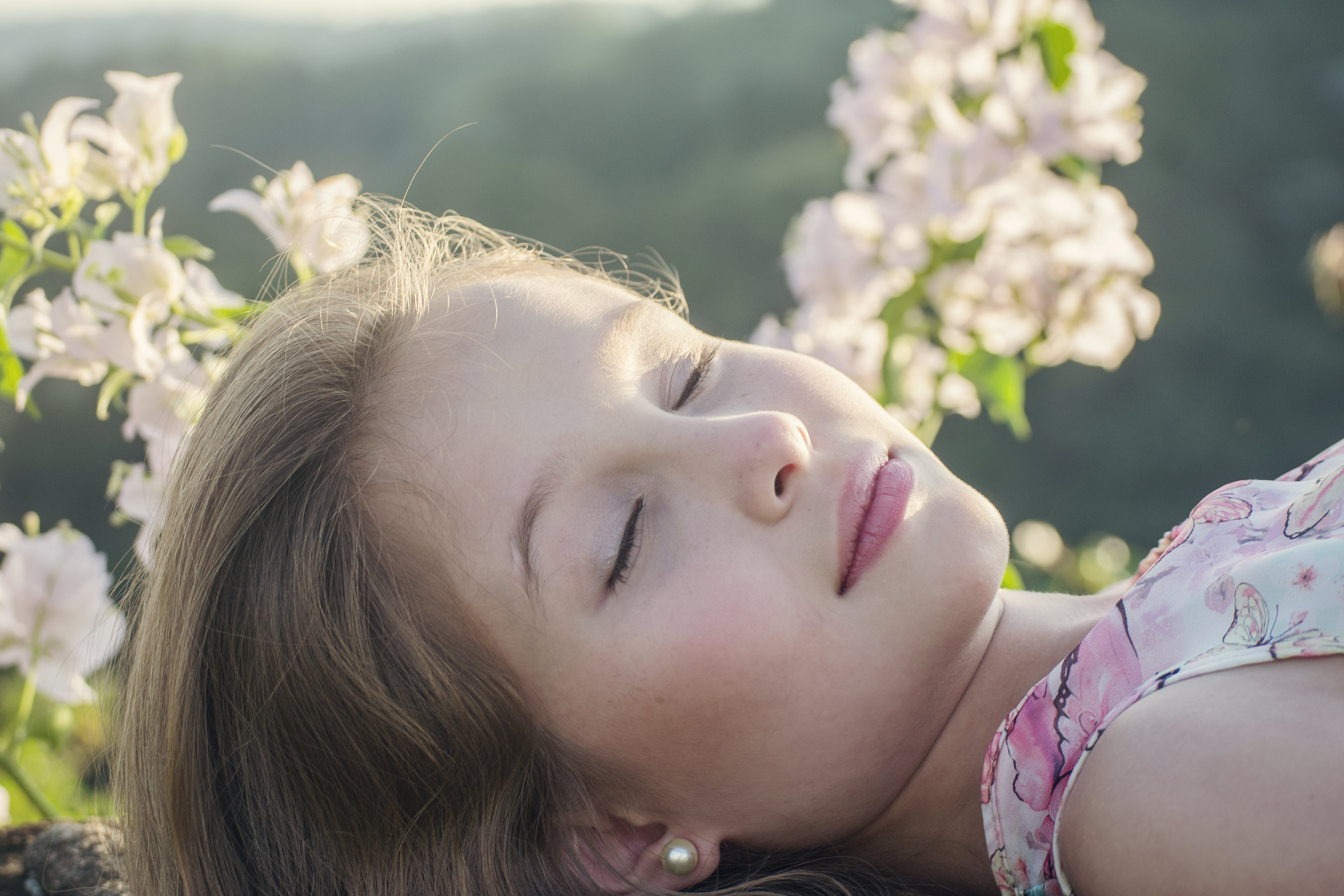 Close-Up Photo of Girl Near Flowers