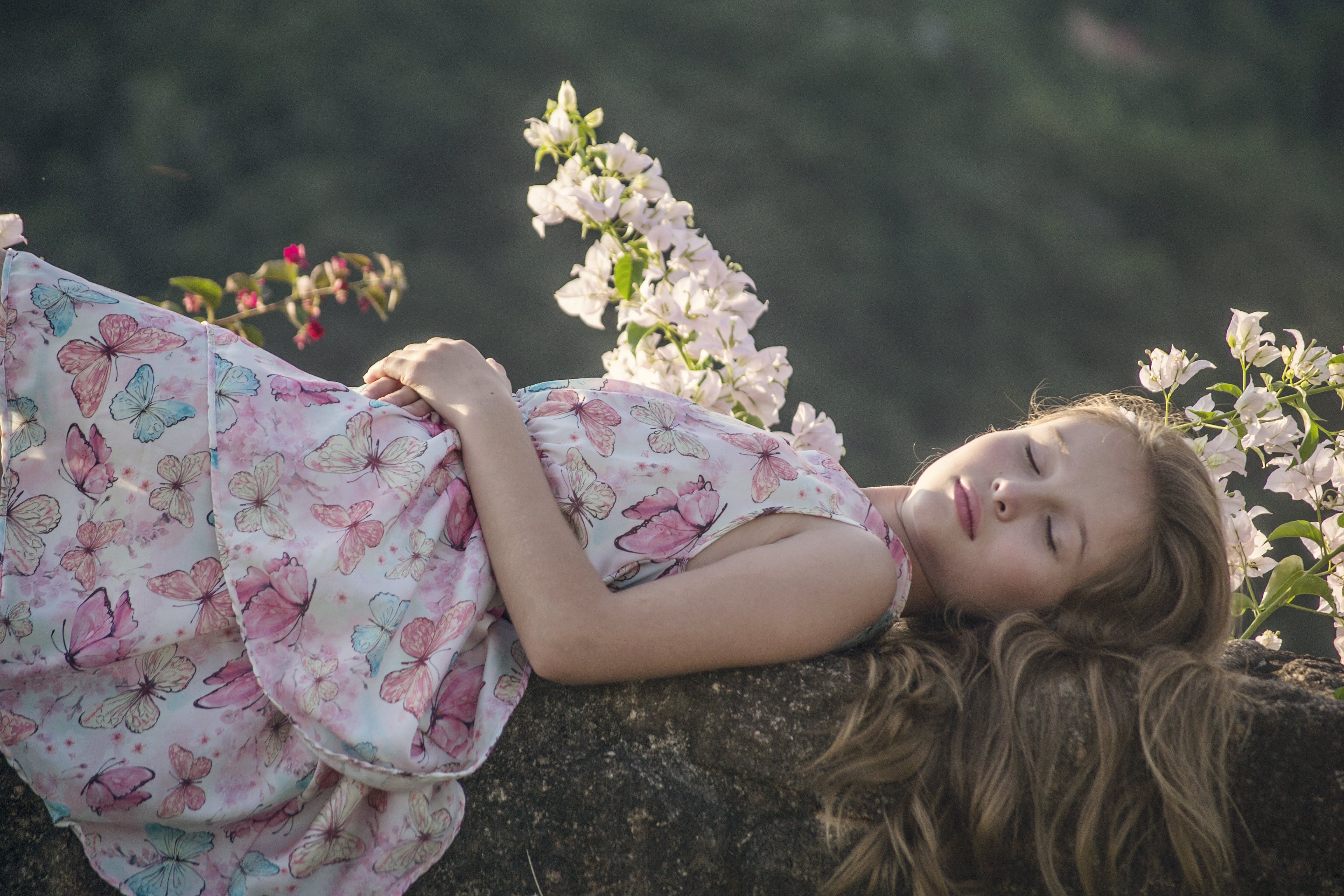 Girl Lying on Rock Beside Flowers