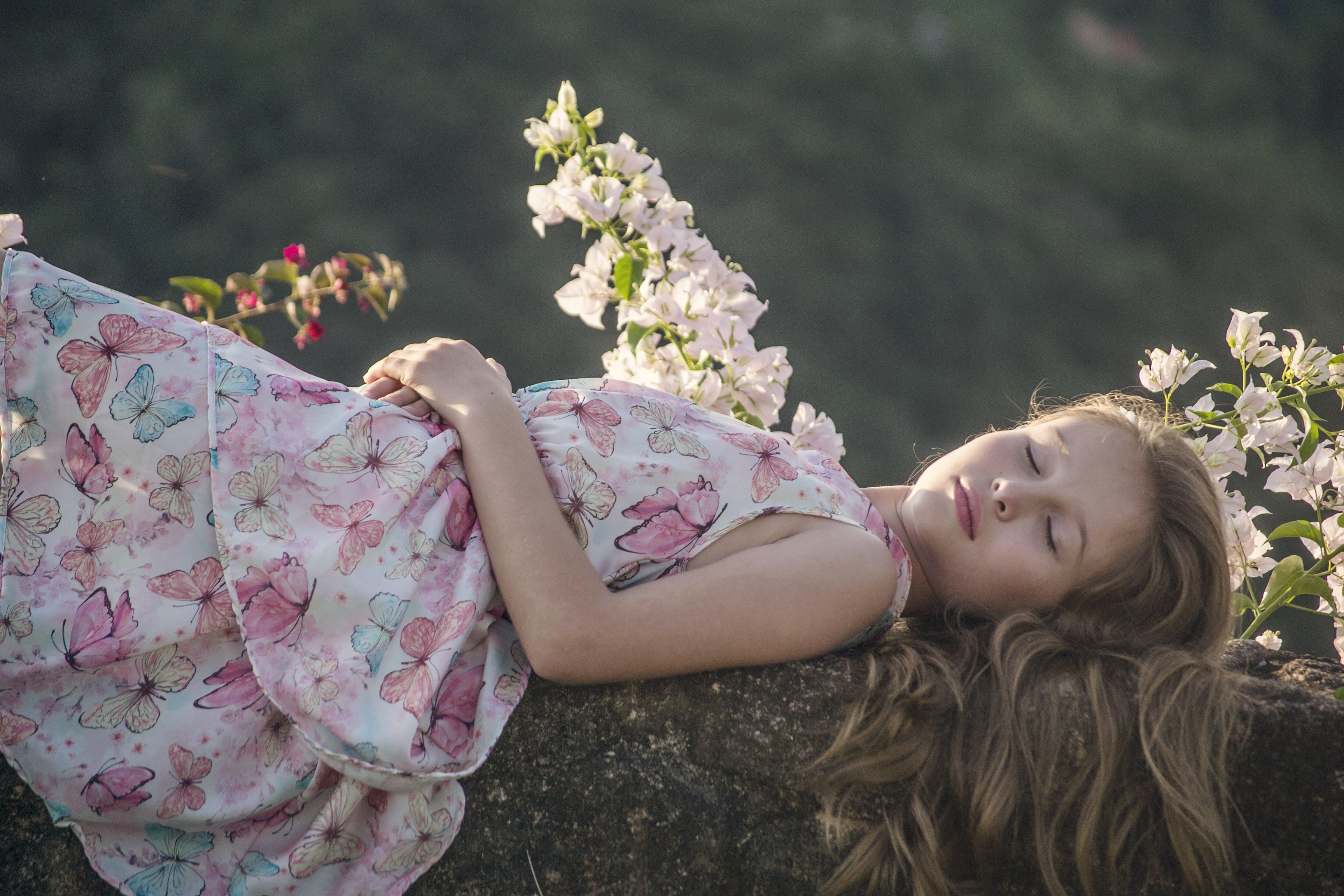 Girl Lying on Rock Beside Flowers