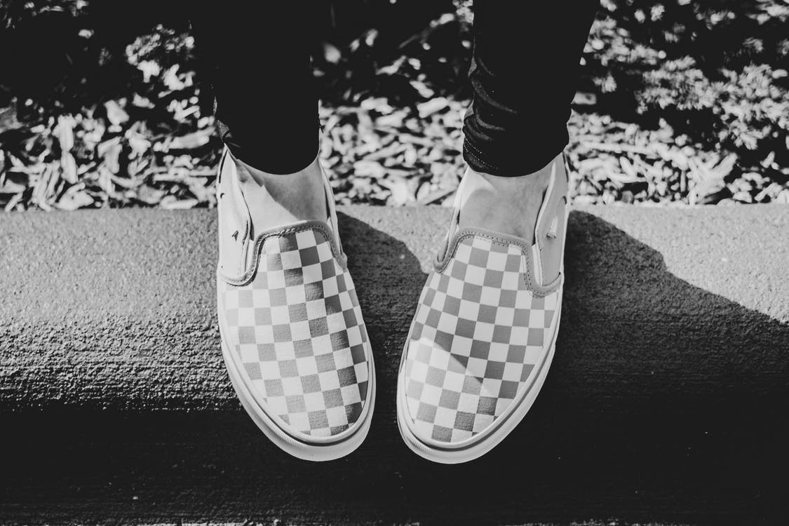 Grayscale Photography of Person Wearing Checkered Slip-on Shoes