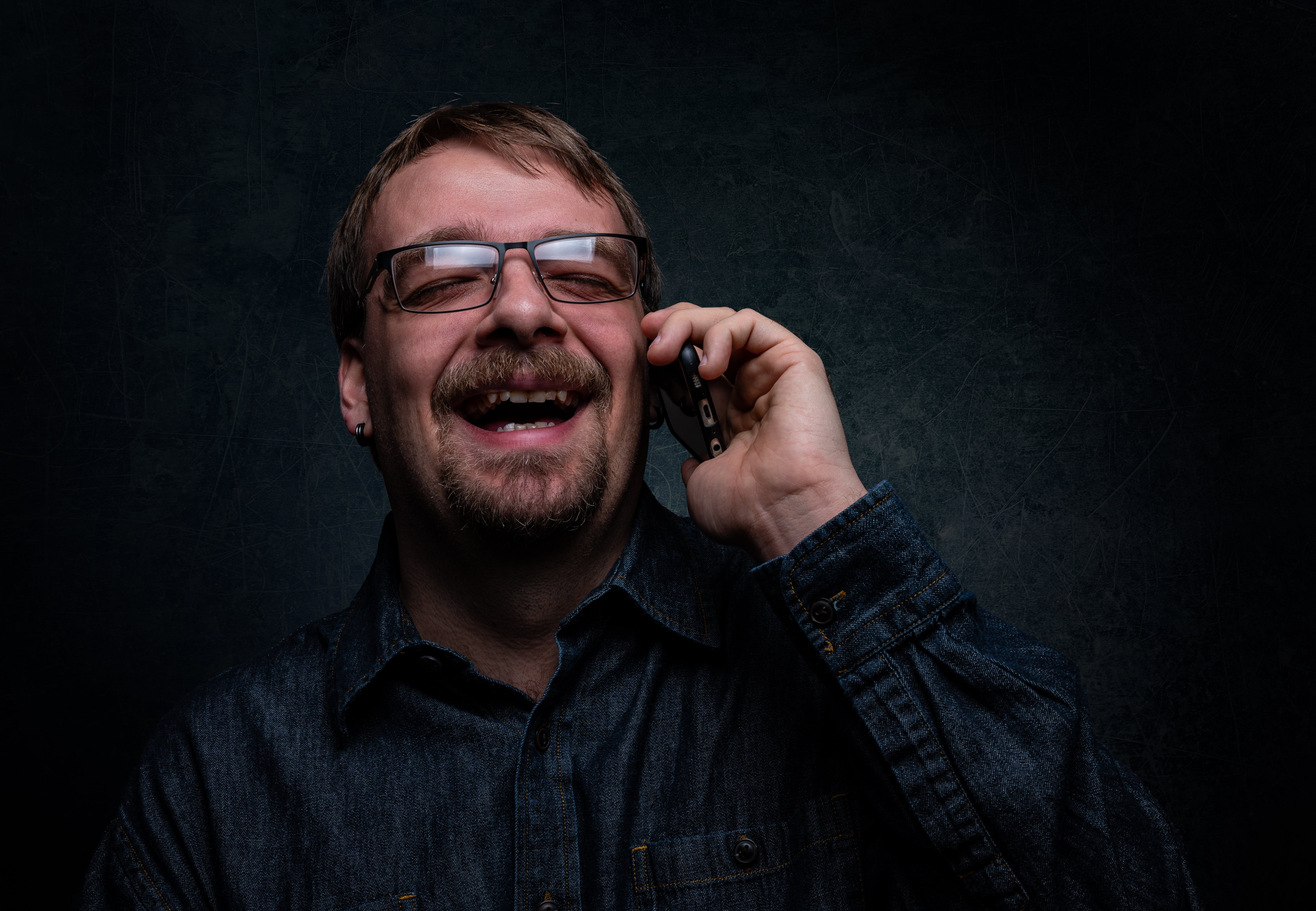 Man Laughing While Using Cellphone