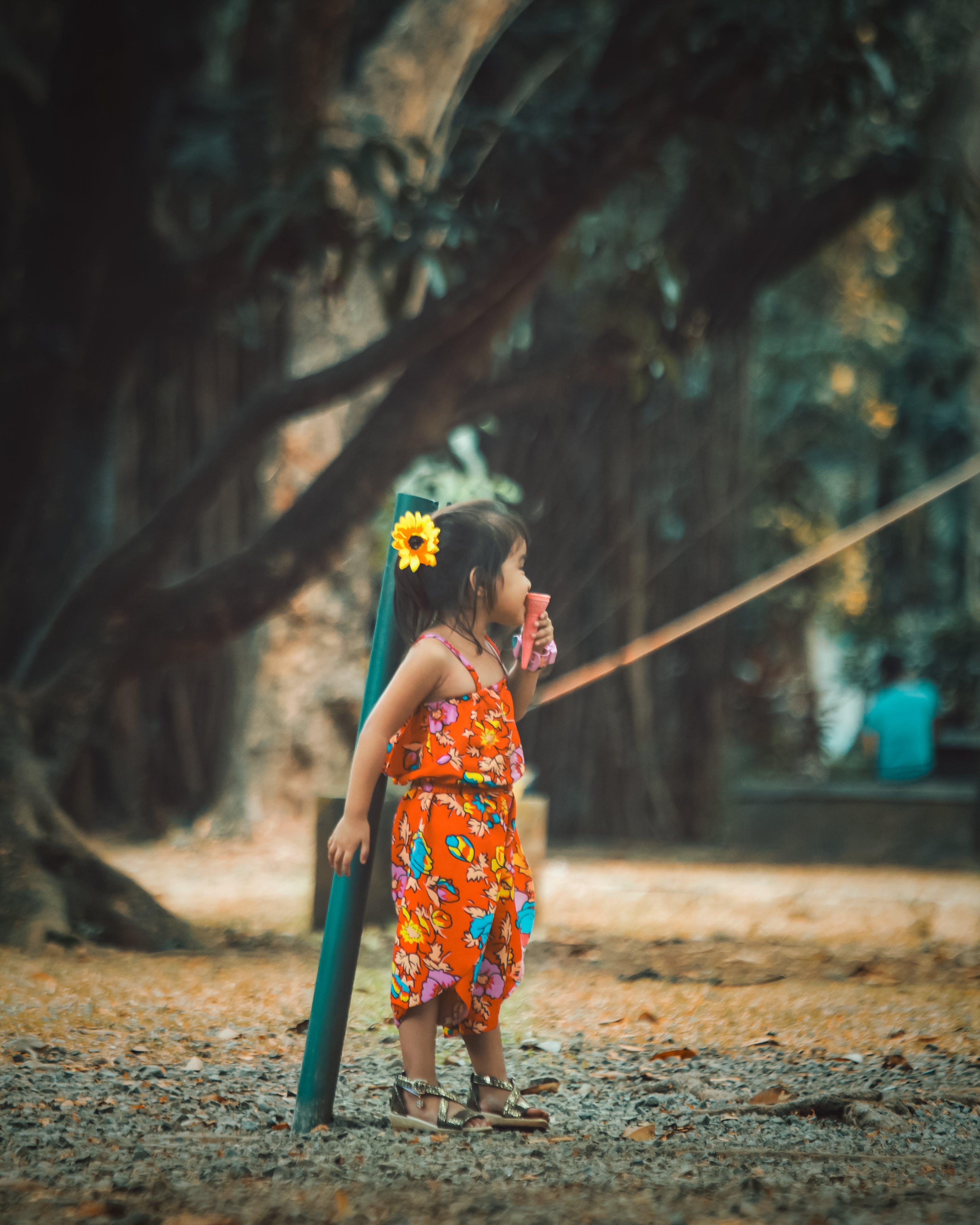 Girl Wearing Orange Floral Jumpsuit