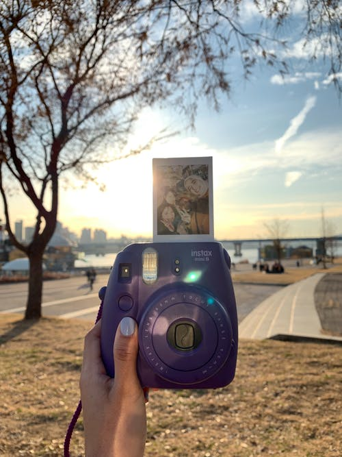 Person Holding Purple Fujifilm Instax Camera With Photo