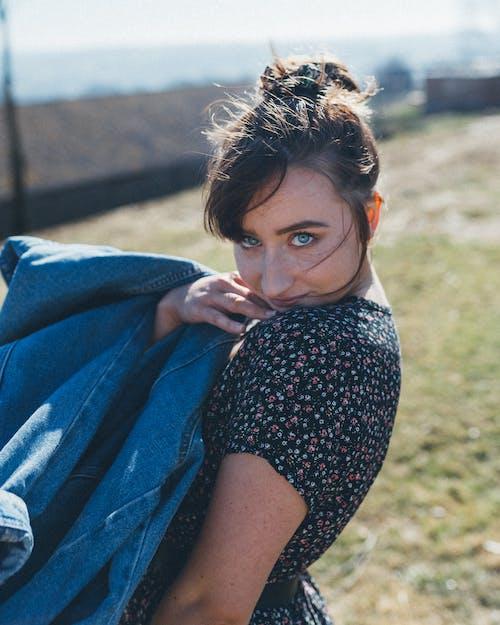 Photo of Woman Holding Blue Denim Jacket Posing