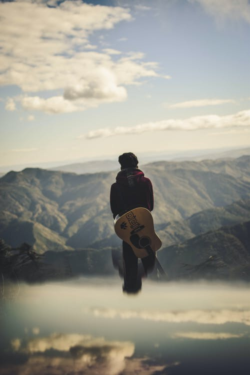 Man Carrying Guitar While Standing Starring at the Hills