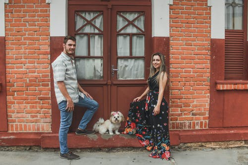 White Dog Between Smiling Man and Woman