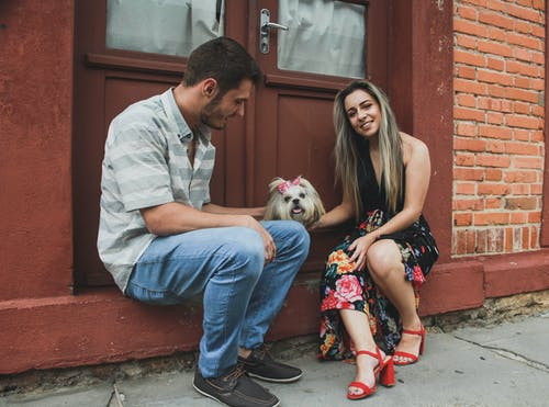 Photo of Smiling Couple Petting a Shih Tzu While Sitting