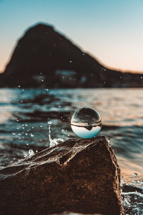 Shallow Focus Photo of Glass Ball Near Body of Water