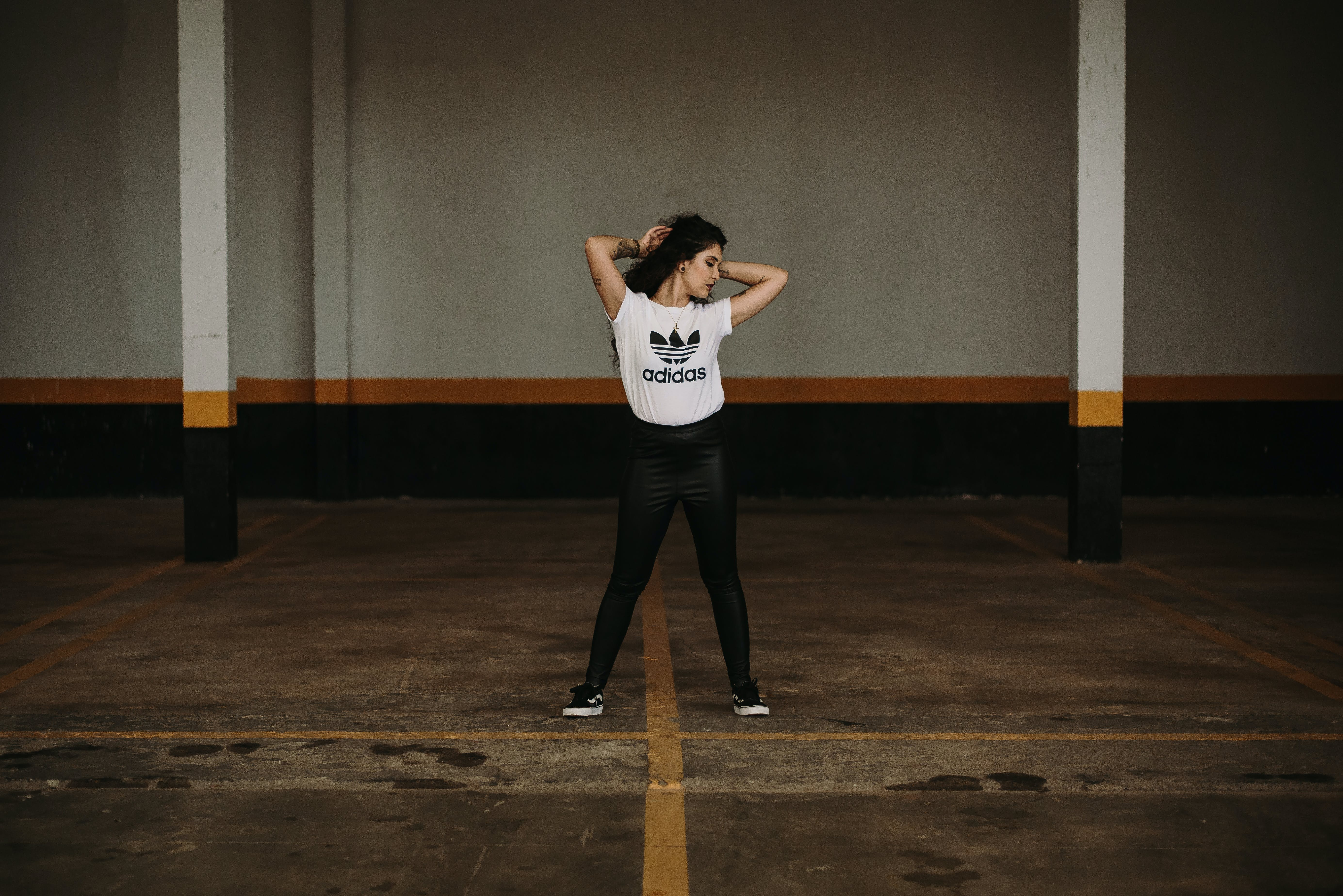 Photo of Woman in White Adidas Shirt Posing in the Middle of a Parking Lot
