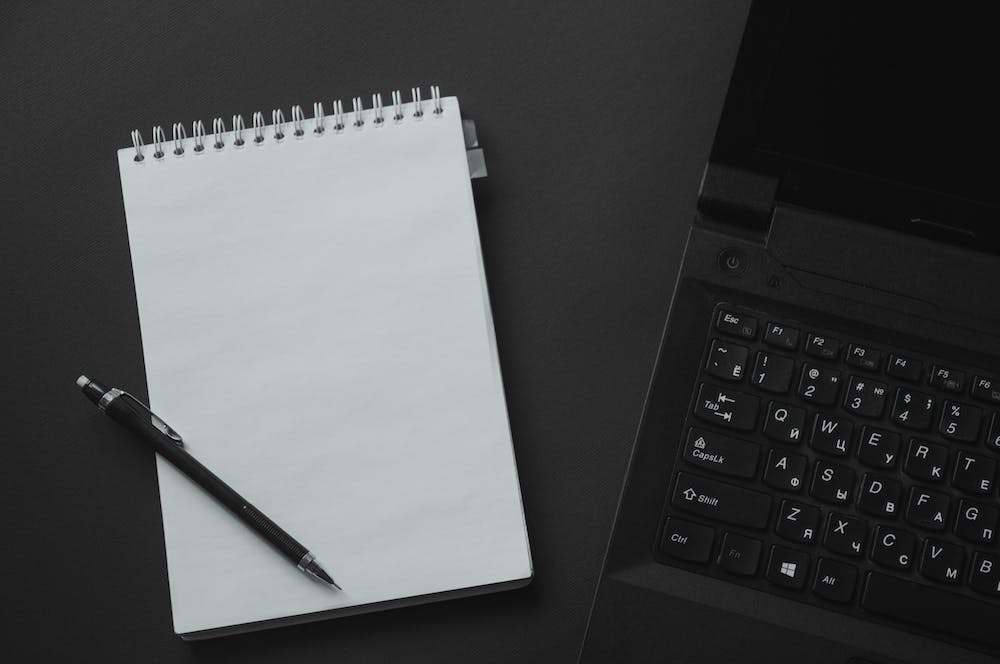 A pen and notepad beside the laptop. | Photo: Pexels