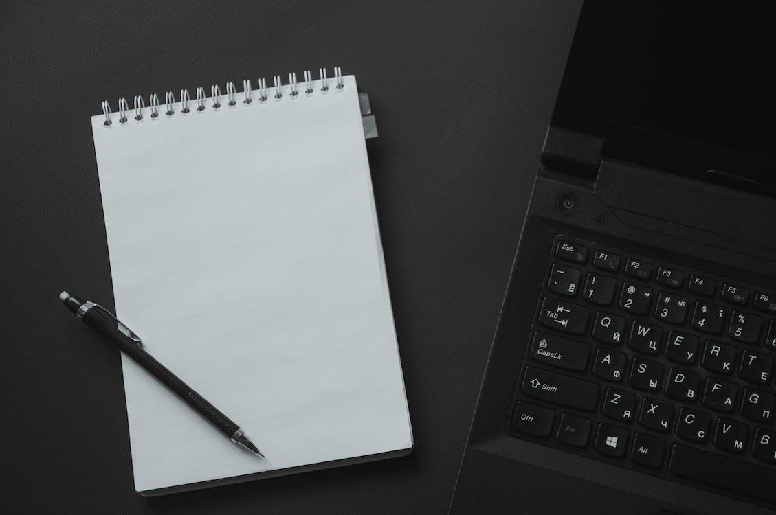 Black Laptop Computer Beside White Steno Notebook