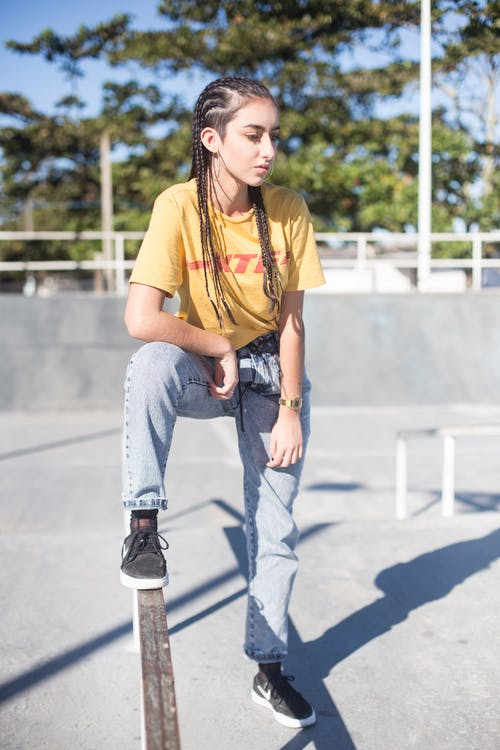 Woman With Braided Hair Wearing Yellow Shirt and Jeans at the Park