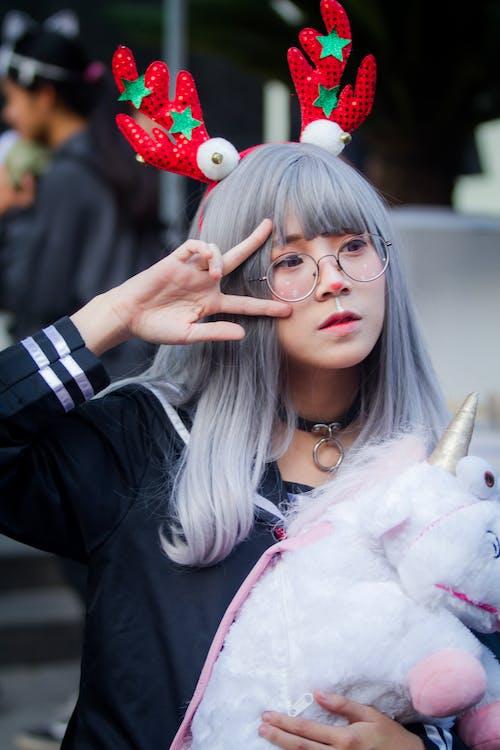 Woman Holding Unicorn Plush Toy Making Peace Hand Sign
