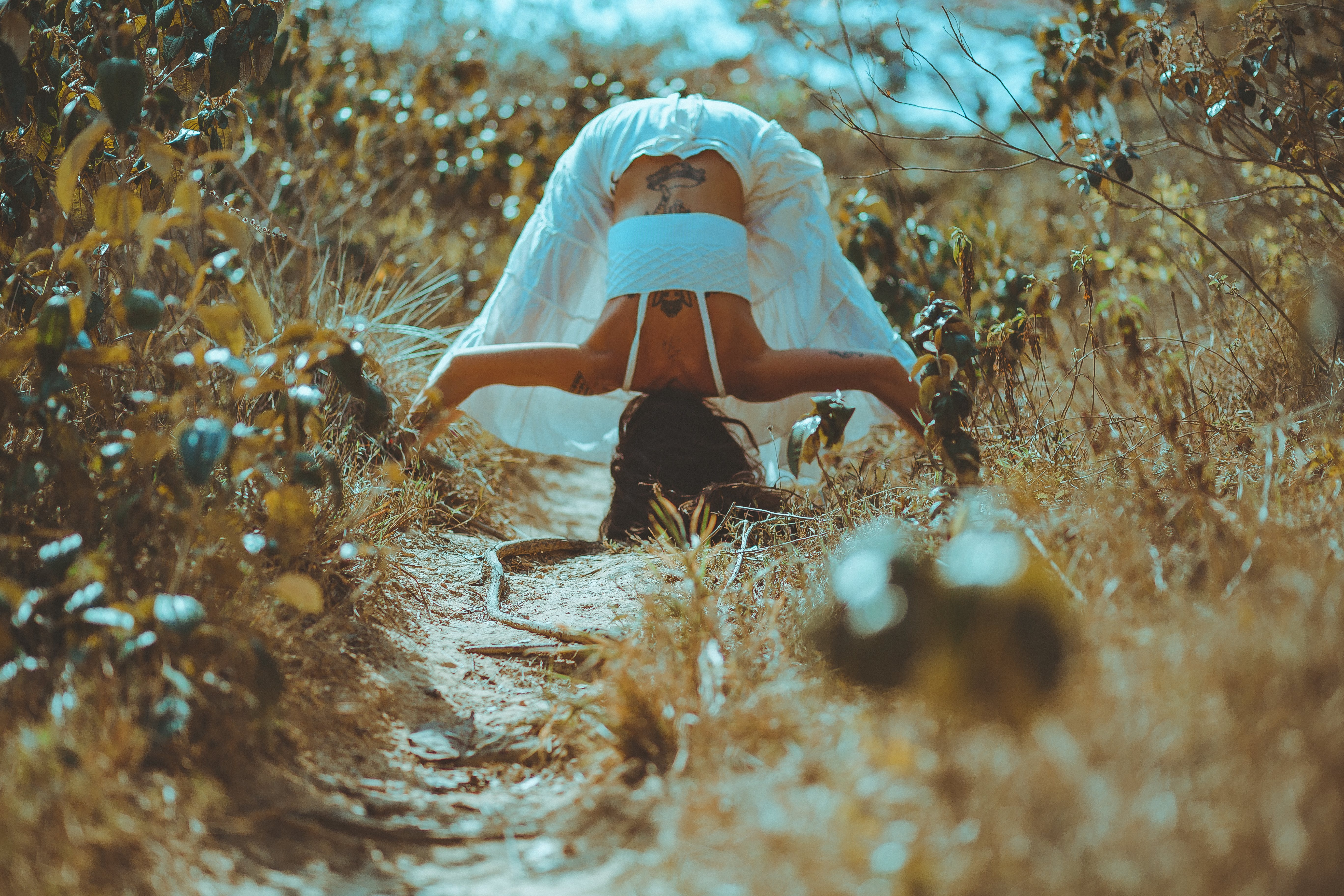 Woman Wearing White Dress Doing Head Stand