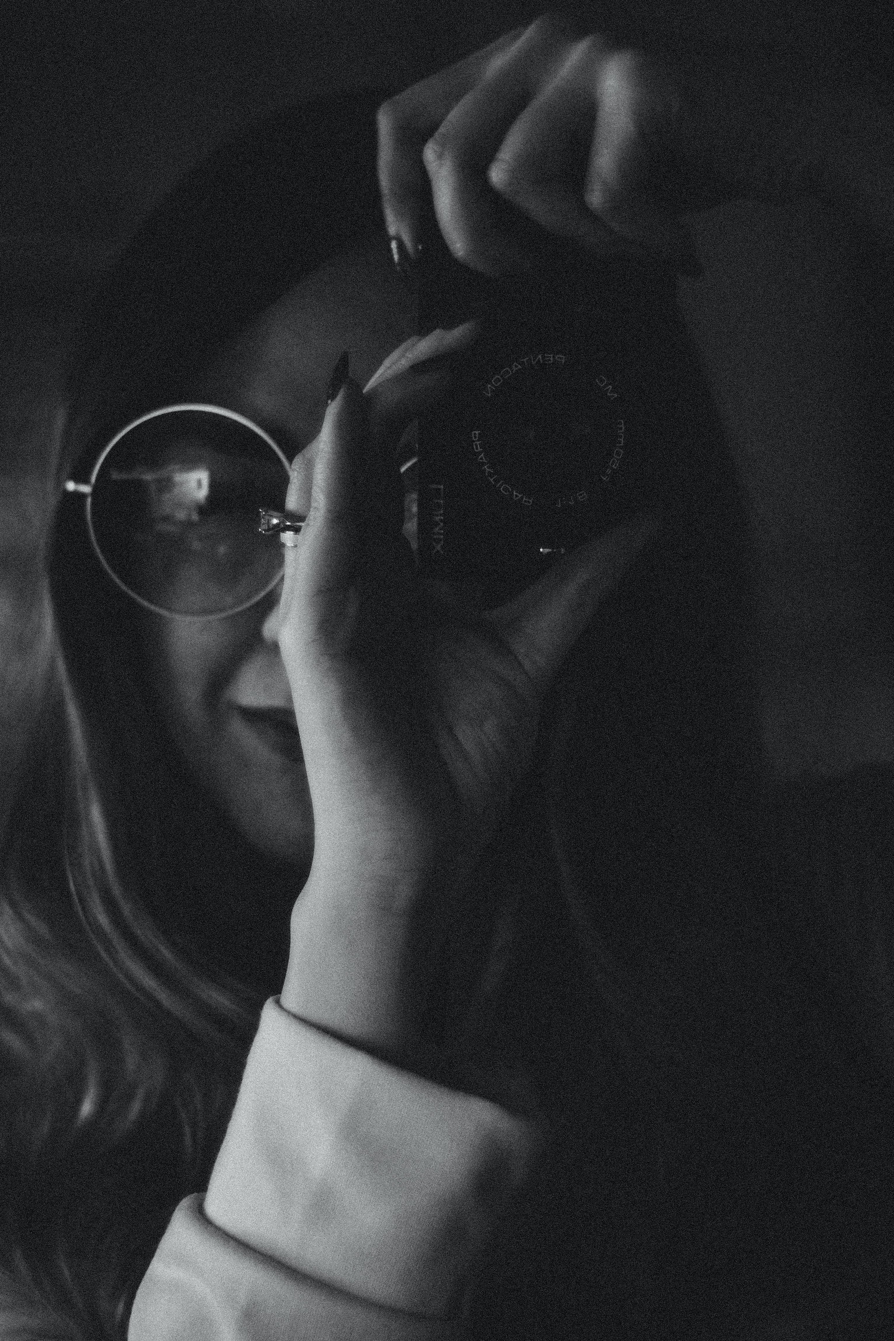 Monochrome Photo of Woman Using Camera