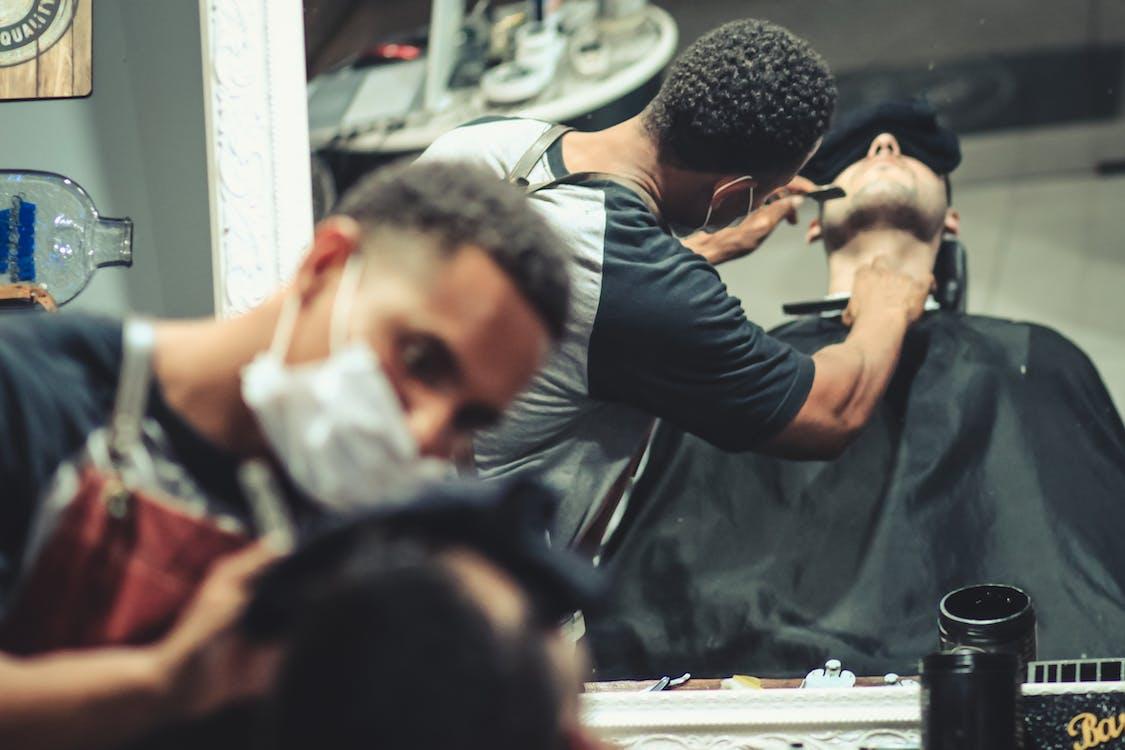 Mirror Reflection of Man Shaving Man's Beard