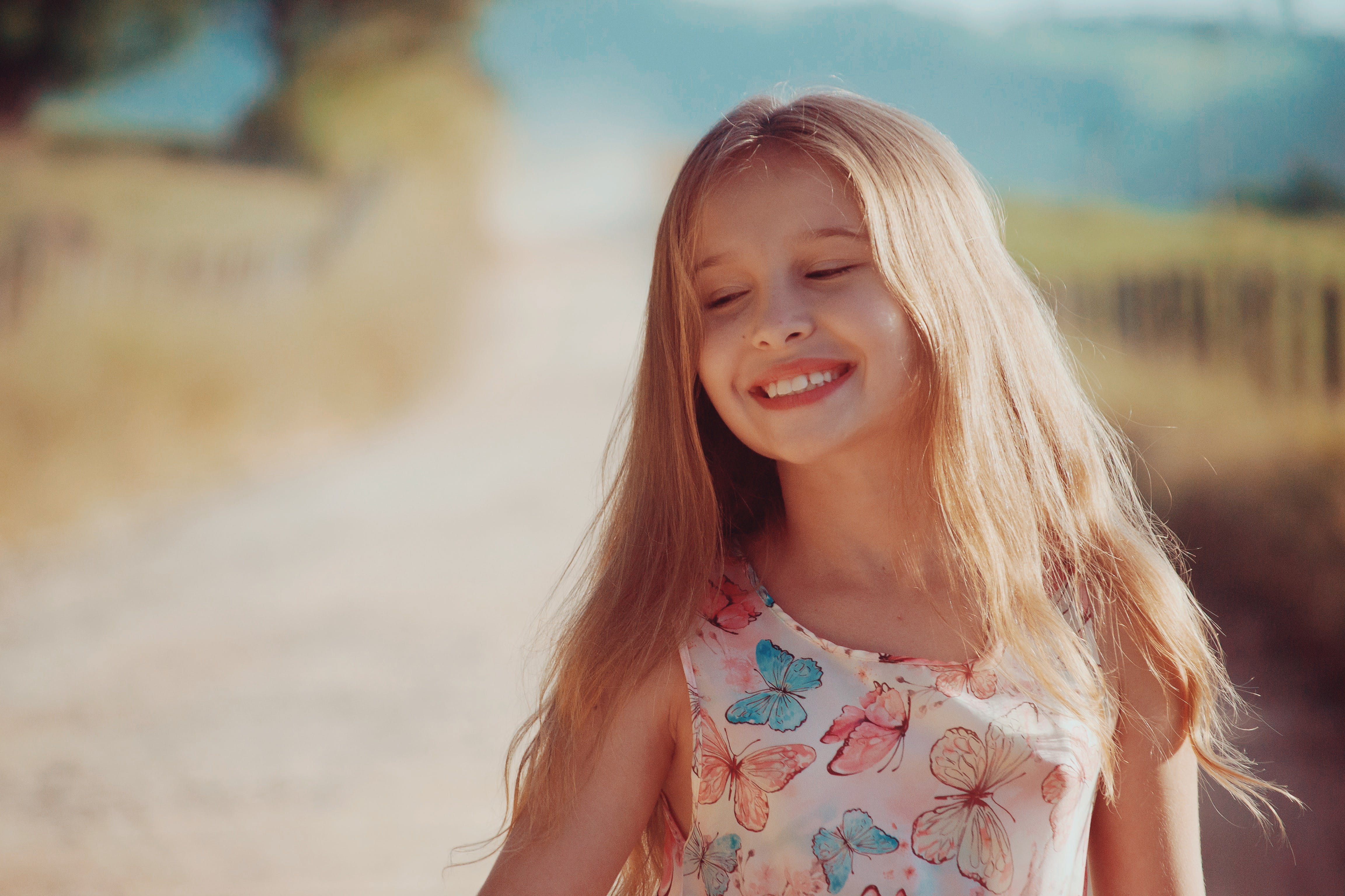 Girl Wearing Butterfly Printed Dress Smiling