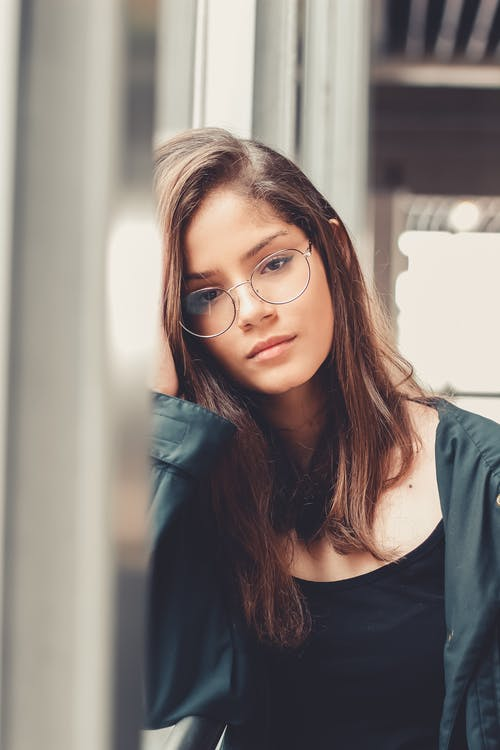 Photo of Woman in Eyeglasses Leaning on Window Sill