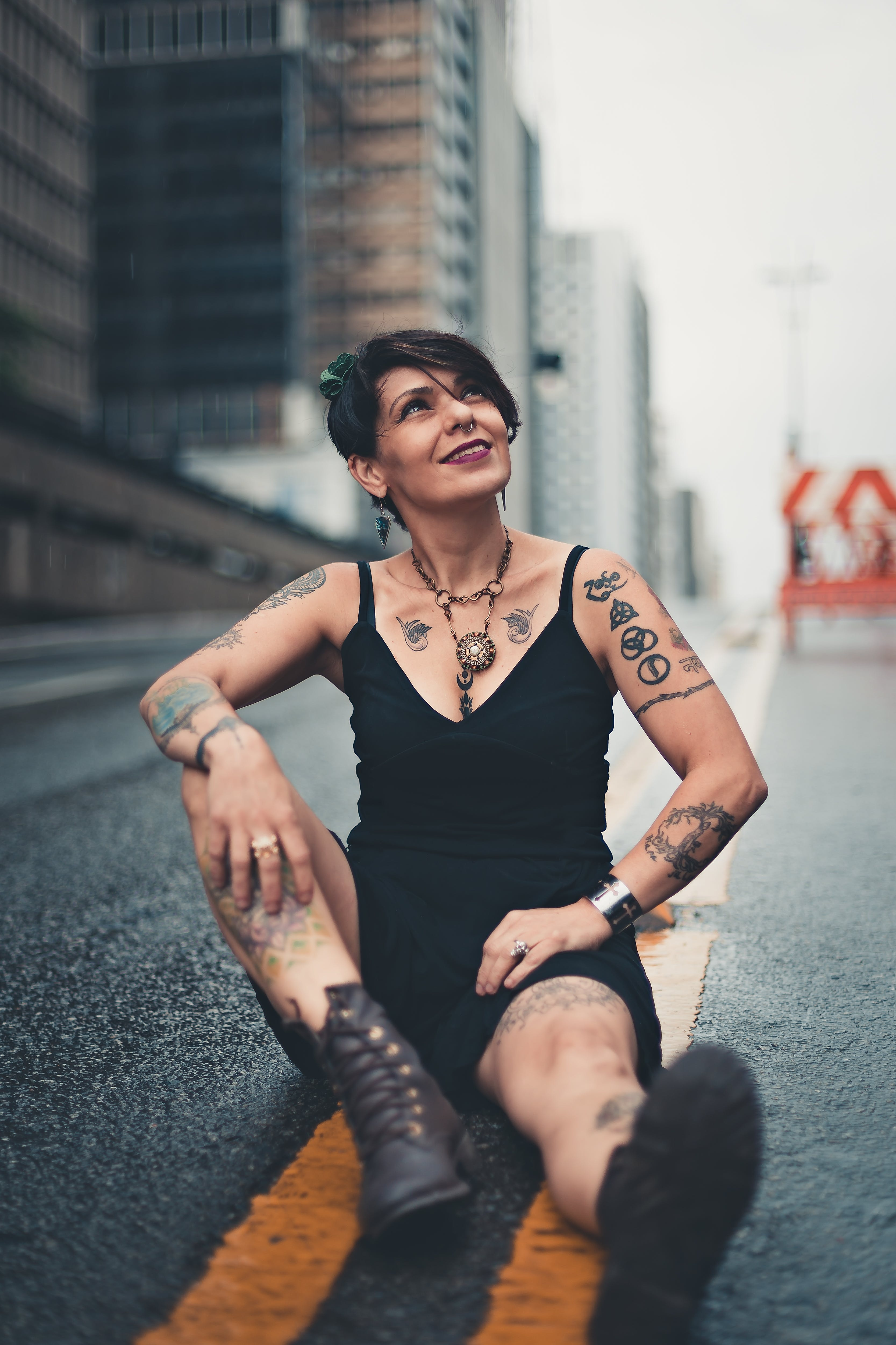 Photo of Smiling Woman Looking up Sitting on Concrete Road