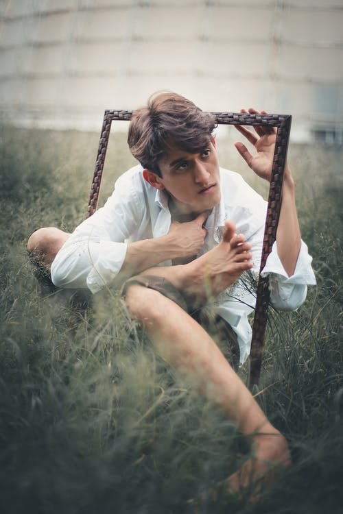 Man in White Dress Shirt Holding Frame Sitting on Green Grass Covered Ground