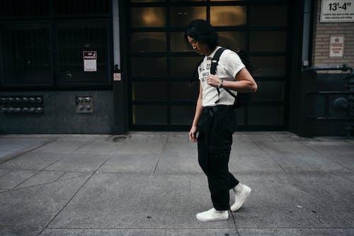 Woman Walking Beside the Building